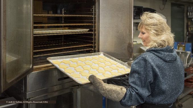 Diane Udell at the oven, preparing to cook customer Christmas meals for Tippens Specialty Wine & Foods in Lodi Township Michigan